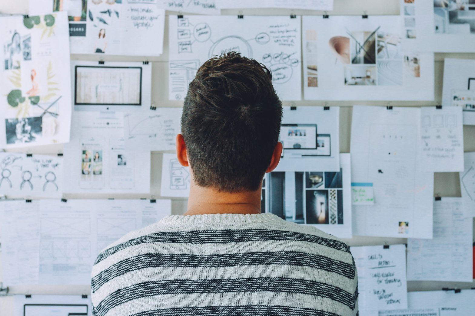 Chico mira su mural de trabajo, para averiguar como ser más productivo y rendir más en el trabajo.