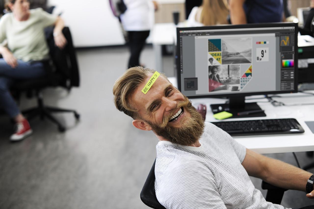 En la imagen aparece un hombre rubio de barba feliz trabajando en su oficina. Representa el artículo cuyo nombre es ¿como buscar trabajo con éxito?