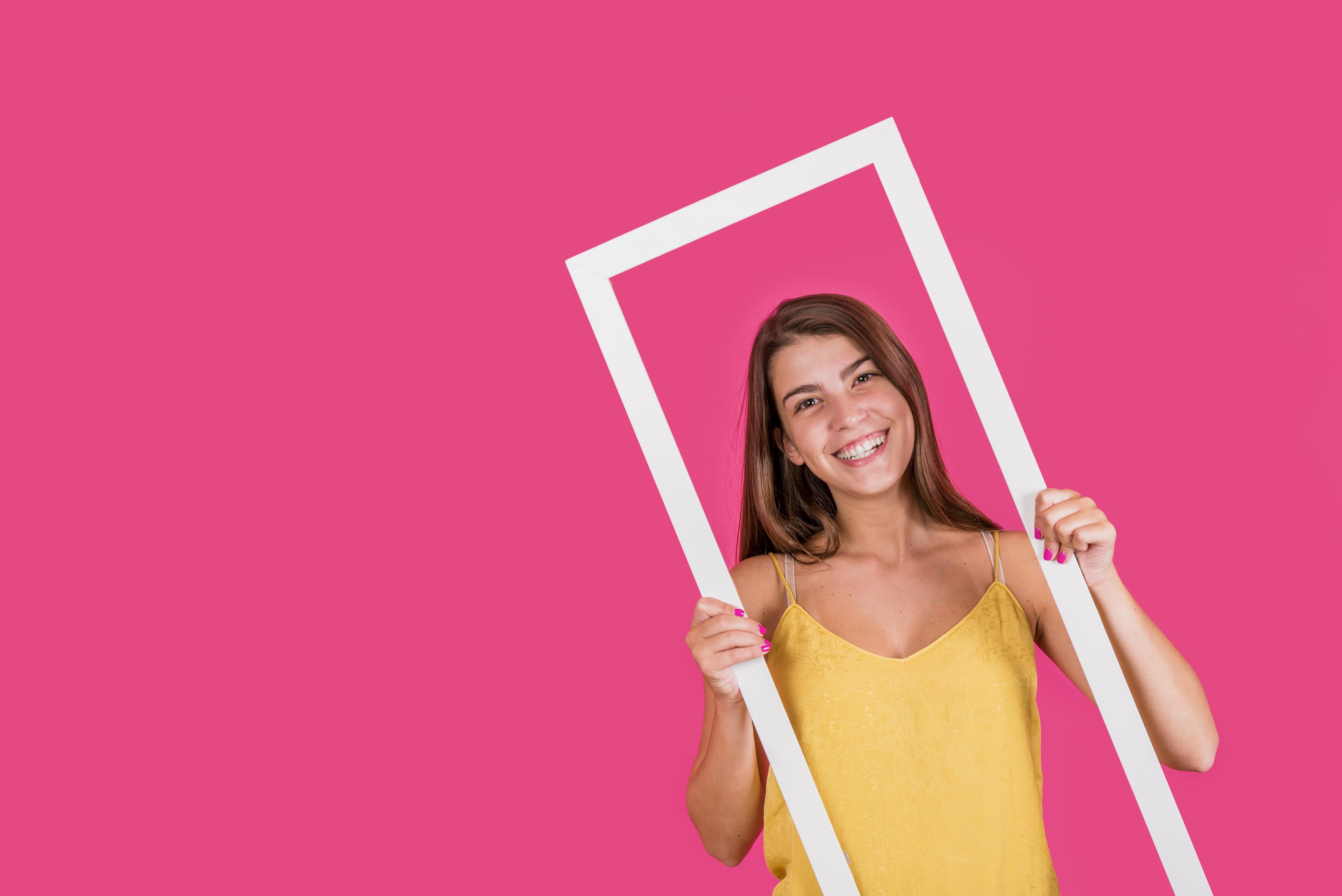 Chica sujeta marco blanco sobre fondo rosa. Como ella son muchos los millennials que buscan empleo a través de diferentes portales de empleo
