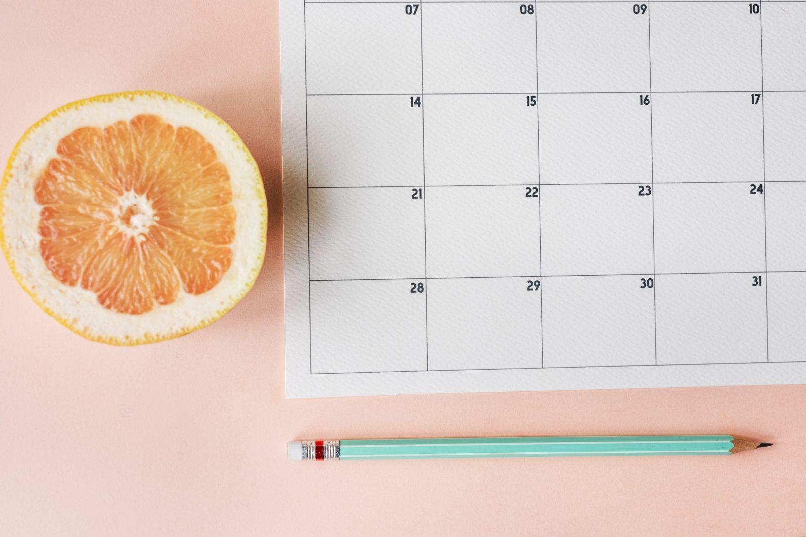 Imagen de un calendario para hacer la organización de tu trabajo y planificación del bullet journal sobre fondo rosa.